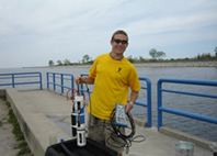Eric Strickler holds a water quality sonde near the Muskegon Lake Channel